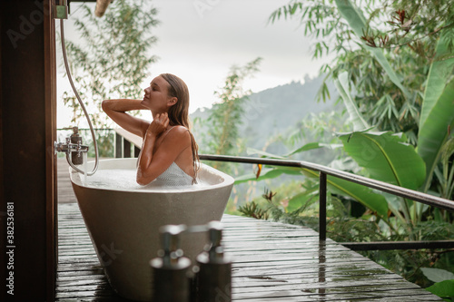 Fotografie, Obraz Young happy woman pampering her body in water while lie in bath tube outdoor wit
