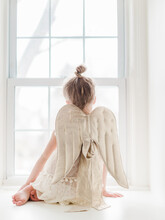 Little Girl Playing Dress Up With Angel Wings Sitting At A Window