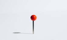 A Red Push Pin Casting A Shadow.