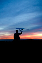 Silhouette Of A Man Holding A Large Remote Control Plane At Sunset