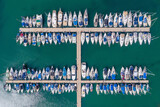 Small Boats and Yachts anchored in a large marina, Top down aerial view.