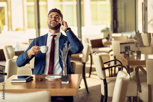 Cheerful businessman talking on the phone while having coffee break in a cafe, Canvas-taulu