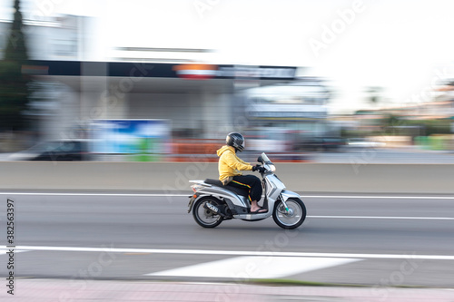 Fotografie, Obraz Barcelona, Spain; May 5, 2017: Panning of one fast scooter in the city