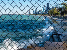View Through Fence Of Waves Spraying Up On Lakefront Of Lake Michigan With View Of Downtown Chicago
