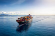 Aerial view of a heavy loaded container cargo vessel traveling over calm, blue sea