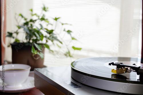Fotomural 陽が射し込む窓辺のレコードプレイヤーで趣味の音楽を聴く