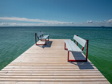 Baltic Sea Pier With Benches Reflect The Opposite Way Of Life