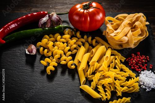 Obraz na plátně Uncooked pasta with vegetables on black stone on wooden background
