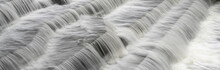 White Water Flowing Over Weir Low-level View At Long Exposure To Give Blurred Motion Effects