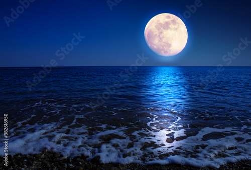 Full moon with reflections on a calm sea at midnight. Fotobehang
