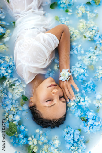 Woman relaxing in bath with tropical blue hydrangea. Beautiful gently caucasian female lying in flowers. Beauty treatment, skin care therapy. Wellness.