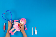 Kid Hands Play Pretend Doctor Game. Toy Stethoscope, Pink Doll And Medicine Tools On Light Blue Background. Top View