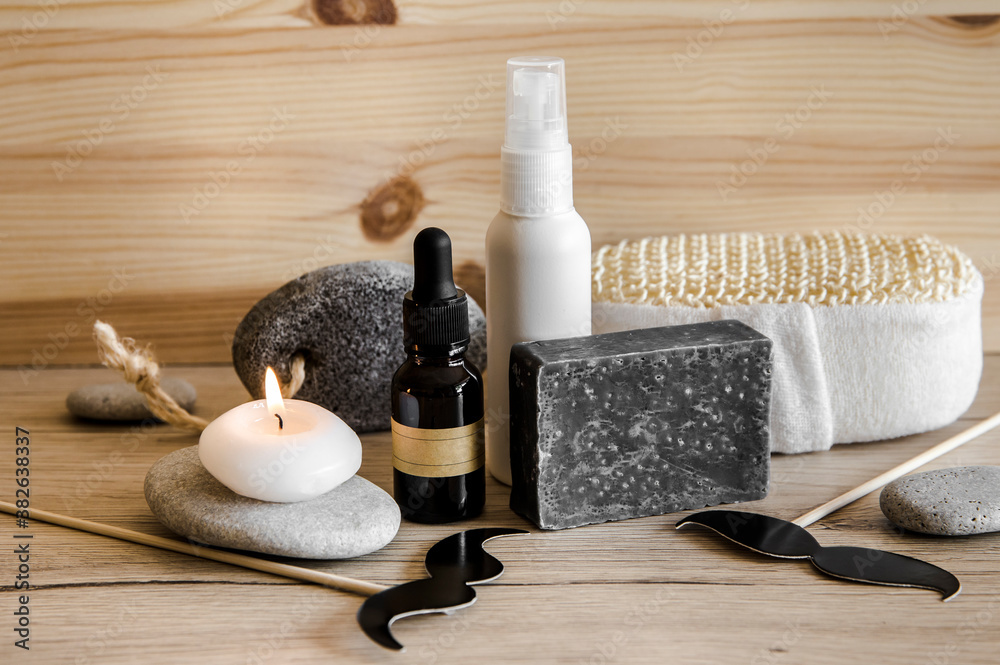 Fototapeta Above view set of various man spa products things. Natural wood disc background with flat sea stones. Gray clay soap bar, beard oil, moisturizing cream, candle burning. Funny mustache shape figurines.