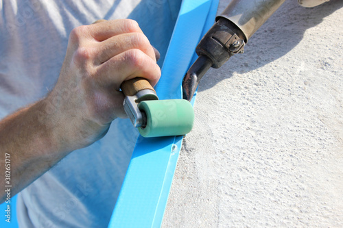 A worker welds plastic cover for water pool Wallpaper Mural
