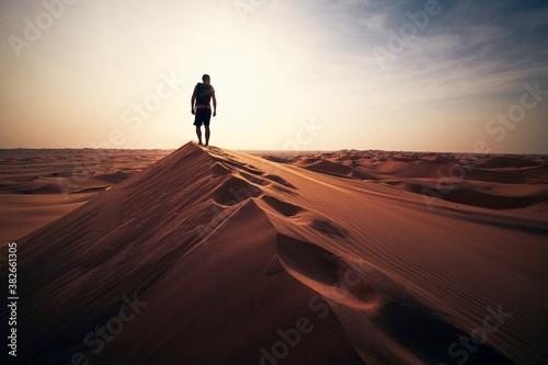 Fototapeta Man walking on sand dune against sunset