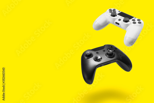 Photo White and black game controllers on yellow background