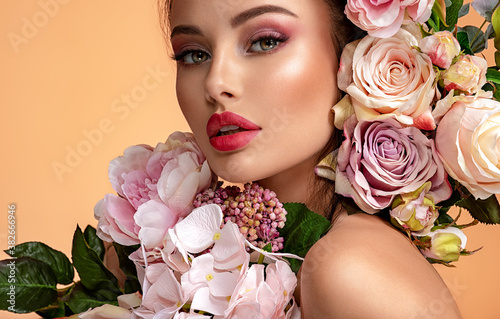 Fototapeta Beautiful white girl with flowers. Stunning brunette girl with big bouquet flowers of roses. Closeup face of young beautiful woman with a healthy clean skin. Pretty woman with bright makeup obraz