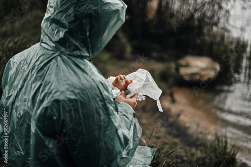 Fotografía A man with a beard in a green raincoat eats in nature