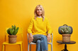 Confident serious female pensioner poses between two chairs with cactus has confident gaze at camera calm expression wears yellow sweater and jeans has rest at home being alone feels melancholic