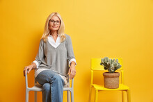 Middle Aged Old Woman Sits On Comfortable Chiar Looks Confidently At Camera Prepares For Job Interview Has Self Assured Expression Isolated On Yellow Background. Senior Lady Spends Free Time Alone