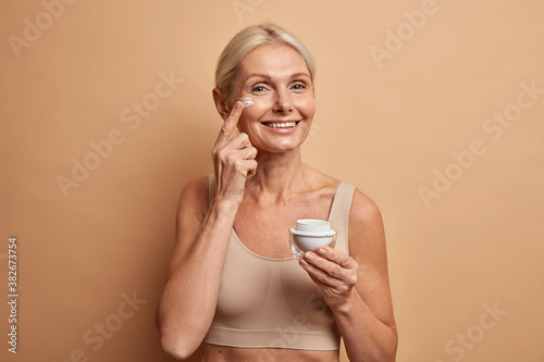 Fototapeta Glad lively European woman of middle age applies anti aging cream on face has na