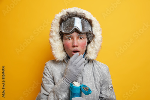 Winter vacation concept. Surprised ethnic active woman enjoys sport activity keeps mouth opened from shock drinks hot beverage dressed in outerwear isolated on yellow studio background. Ski resort