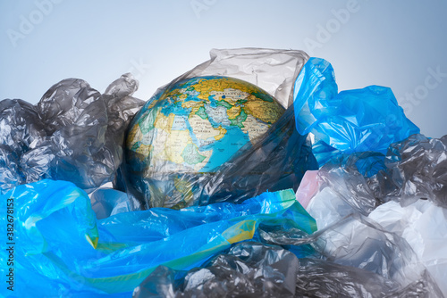 The concept of protecting the world from plastic waste, fighting environmental pollution, the globe lies in a pile of various garbage layouts on a light background Fototapet