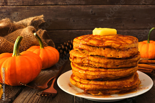Stack of pumpkin spice pancakes with caramel sauce. Side view table scene on a dark wood background. Fall breakfast concept.