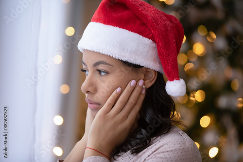 Photo Upset african American young woman in Santa hat look in distance feeling lonely