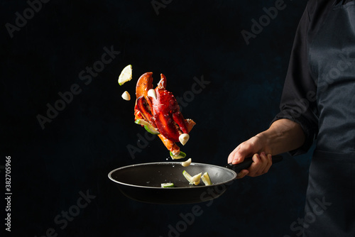 Fotomural The chef toss up king crab legs with pieces of lime in a frying pan on dark blue background