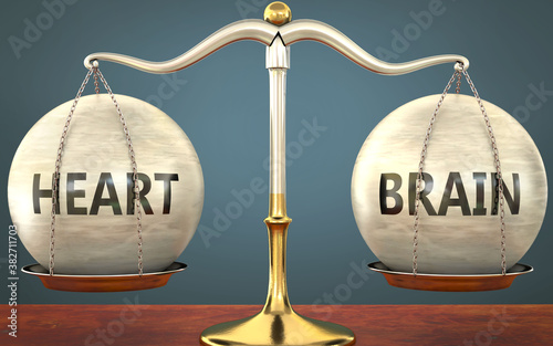 Foto heart and brain staying in balance - pictured as a metal scale with weights and