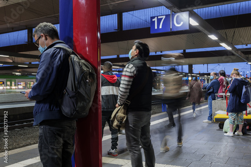 Passengers with protective face mask stand and wait for arrival train on platform of railway station in Germany during epidemic of COVID-19 virus Fotobehang
