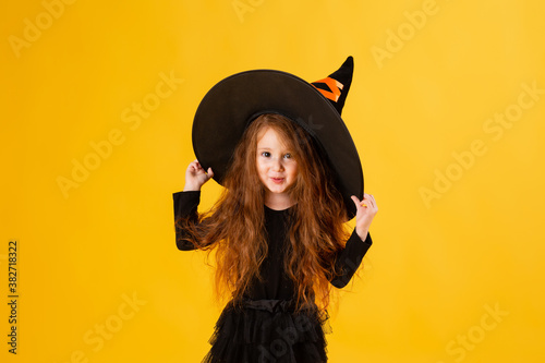 Photo little girl with long red hair smiles in a Halloween witch costume and holds a pumpkin-shaped candy bowl on a yellow background