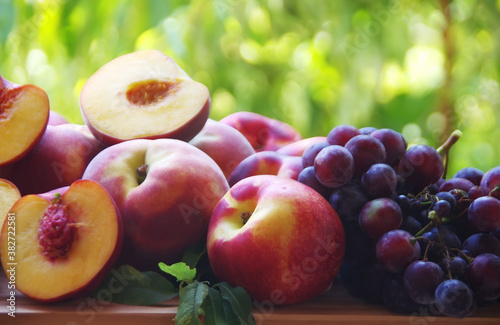 Cuadros en Lienzo ripe peaches and grapes on wooden table