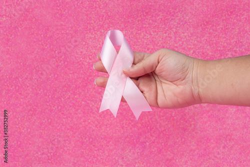 fondo rosado con escarcha y una mano con lazo rosado del cáncer de mama Canvas Print