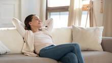 When All The Work Is Done. Carefree Confident Millennial Female Or Teenage Girl Student Enjoying Moments Of Tranquility And Comfort Relaxing On Sofa Indoors Switching On Air Conditioner And Humidifier