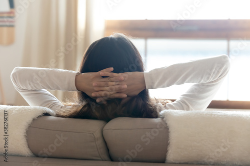 Amazing siesta. Back shot of carefree young woman sitting on soft couch with hands behind head taking break from daily routine, enjoying solitude and being by herself, meditating, breathing fresh air