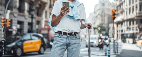 Foto Young traveling woman with suitcase on a sunny city street