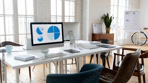 Fototapeta Empty coworking desk with modern PC gadget in loft design office