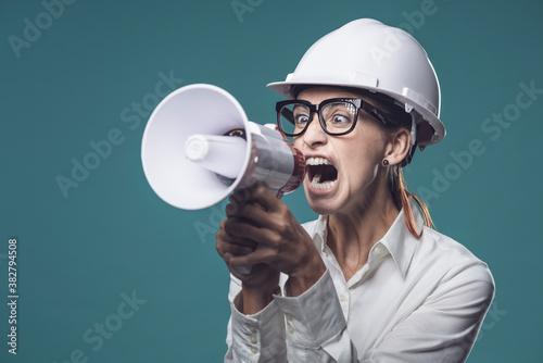 Valokuvatapetti Aggressive businesswoman shouting through a megaphone