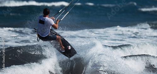 Obrazy Kitesurfing  athletic-man-jump-on-kite-surf-board-on-a-sea-waves