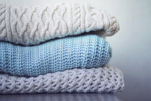 On The Gray Table, Three Warm Wool Sweaters With Different Patterns Are Stacked In A Pile, Ready For The Cold. Winter Time.