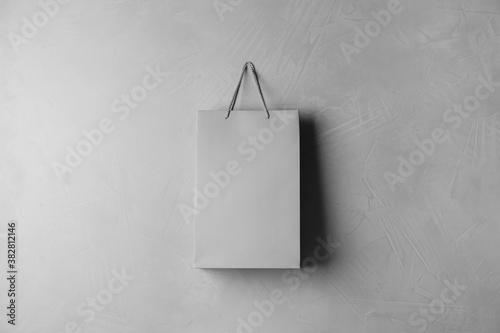 Paper shopping bag hanging on grey wall Fotobehang