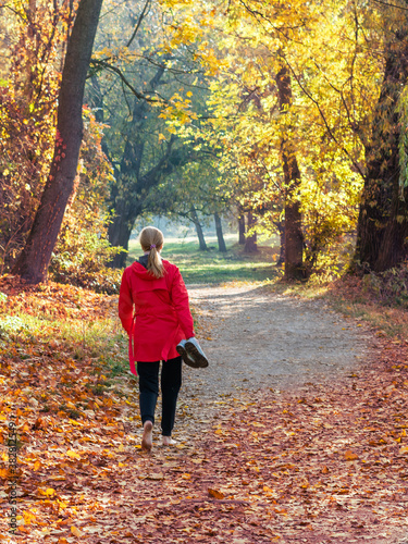 Fototapeta A girl in a red jacket walks barefoot along a path in an autumn park