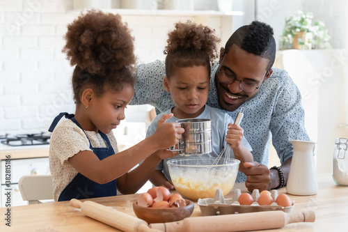 Obraz na plátně Happy young african american dad watching two adorable mixed race kids siblings preparing dough for homemade pastry, enjoying weekend family activity together in kitchen, culinary recipe concept