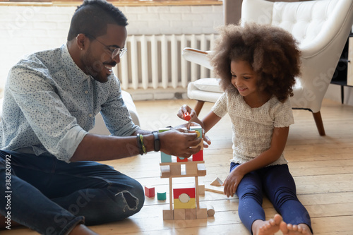 Happy young african ethnicity daddy helping small adorable joyful kid daughter constructing building with wooden blocks, playing on warm floor in living room, enjoying free weekend time at home Canvas-taulu
