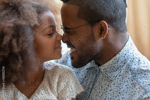 Close up head shot adorable small biracial preschool kid daughter touching noses with affectionate caring young father Wallpaper Mural