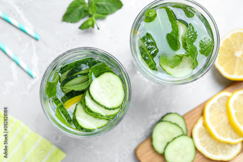 Refreshing water with cucumber, lemon and mint on light grey table, flat lay