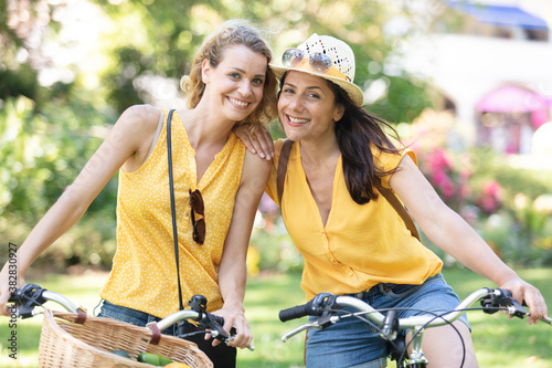 two young women cycling together Fotobehang