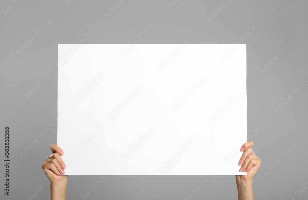 Fototapeta Woman holding white blank poster on grey background, closeup. Mockup for design